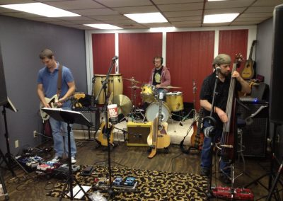 Musicians playing electric guitar, bass, and drums at Anderson Music Studios.