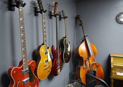 Guitars and bass guitars shown hanging on the wall next to an upright double bass and piano at Anderson Music Studios.